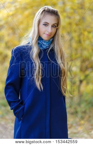 A girl with long blonde hair in a blue coat, yellow autumn background, bokeh