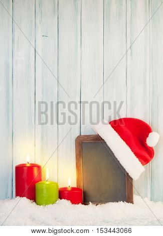 Christmas candles and chalkboard with santa hat in snow. View with copy space