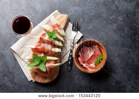 Fresh melon with prosciutto and mint. Antipasti and red wine. Top view on dark stone table