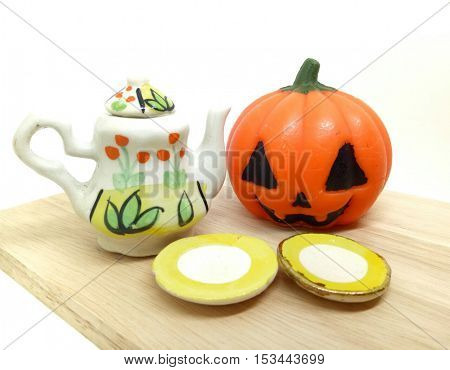 Tea time, Halloween Pumpkin with vintage teapot set yellow color with flower screen on white background.