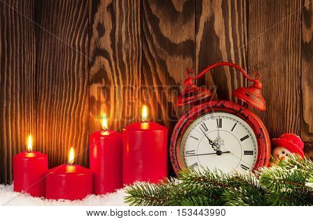Christmas background with candles, alarm clock and snowman in front of wooden wall with copy space