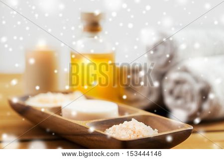 beauty, spa, bodycare, natural cosmetics and bath concept -soap with himalayan salt and scrub in wooden bowl on table over snow