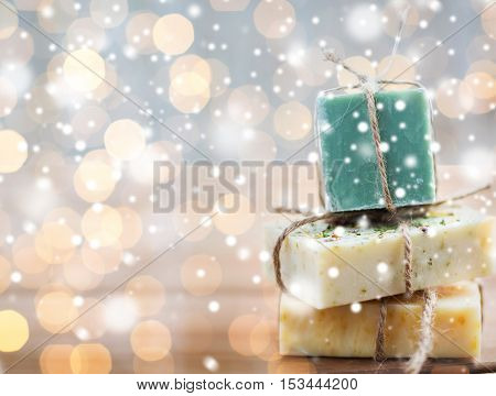 beauty, spa, bodycare, bath and natural cosmetics concept - close up of handmade soap bars over lights and snow