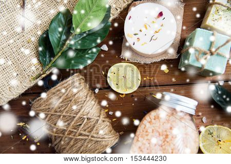 beauty, spa, therapy and wellness concept - natural body care cosmetics on wood over snow