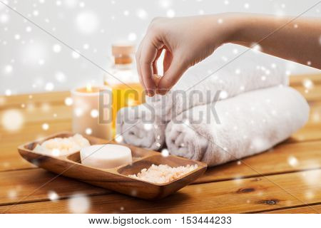 beauty, spa, bodycare and natural cosmetics concept - hand pouring himalayan salt in wooden bowl with soap, scrub and bath towels on table over snow