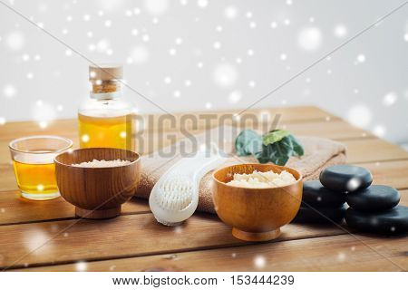 beauty, spa, bodycare, natural cosmetics and massage concept - body scrub with brush and massage oil on wooden table over snow