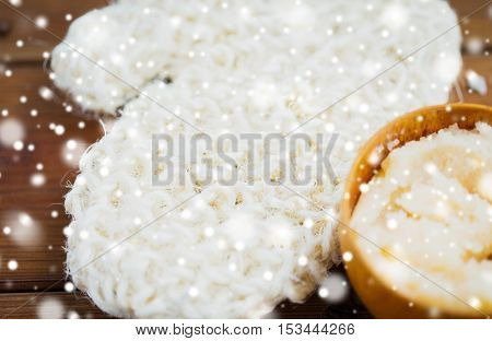 beauty, spa, bodycare, bath and natural cosmetics concept - close up of wisp and body scrub in cup on wooden table over snow