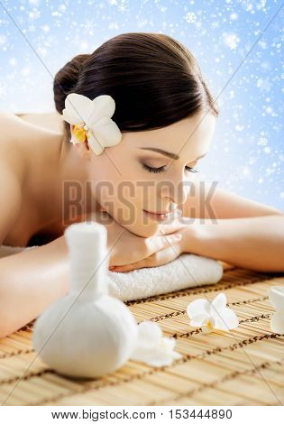 Young and beautiful girl relaxing in Christmas spa salon. Massage therapy over seasonal winter background with snowflakes. Healing medicine and health care concept.
