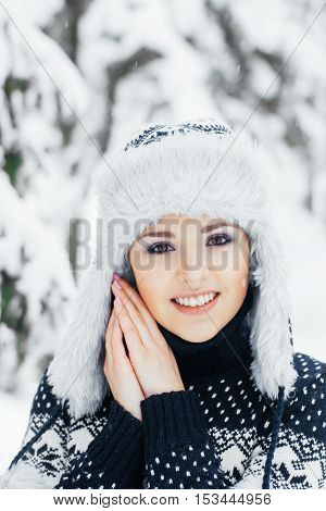 Portrait of young and beautiful girl walking in winter forest. Christmas seasonal concept.