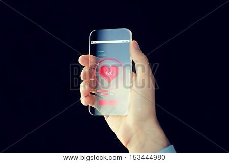 technology, health care, application and people concept - close up of male hand holding and showing transparent smartphone with red heart icon on screen and measuring pulse over black background