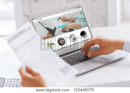 business, technology, internet shopping and people concept - close up of businessman with online shop web page on laptop computer screen working at office