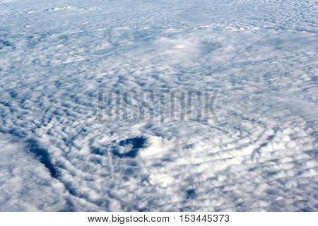 Flying above a dense layer of white clouds in the sunshine in a travel weather and climate concept