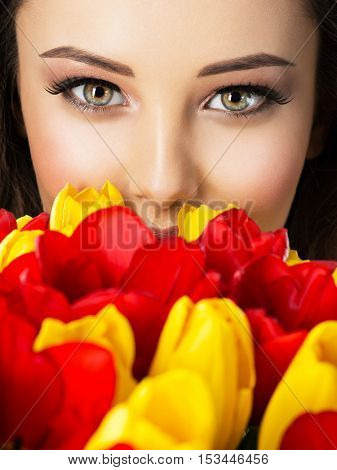 Beautiful woman's eyes among flowers. Portrait of an Attractive girl covers face with red and yellow tulips