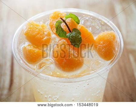 Glass Of Orange Soda On Wooden Table In Coffee Shop