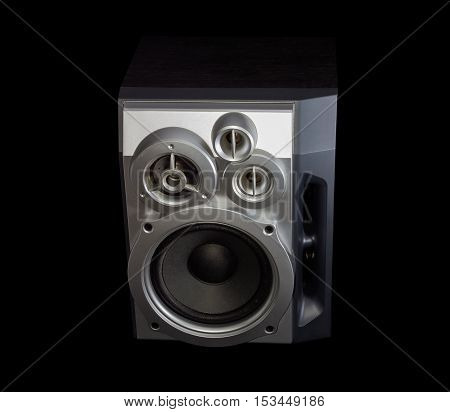 Home high fidelity three-way loudspeaker system with bass reflex port in silvery housing on a dark background