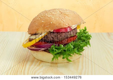 Traditional hamburger with beef patty vegetables and condiments on a light wooden surface