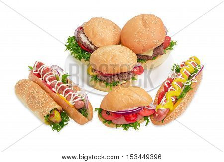 Three different hamburgers with beef patty and vegetables on a white dish and several different hot dog with frankfurter mustard ketchup and vegetables on a light background