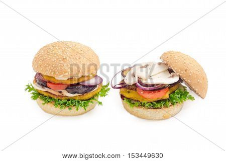 Two vegetarian burger with filling of two lentil patties lettuce tomato onion eggplant mushrooms and condiments on a light background