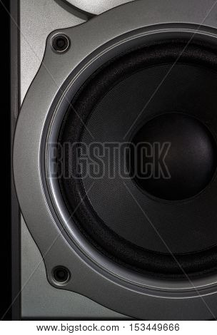 Fragment of a woofer of a home loudspeaker in silvery housing closeup on the dark background