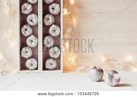 Christmas soft home decor of silver apples and lights burning in boxes on a wooden white background. Xmas background.