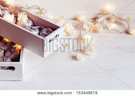 Christmas soft silver apples and lights burning in boxes on a wooden white background. New Year postcard. Xmas background.