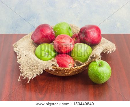 Pile of a red and green apples on a sackcloth in a small wicker basket on a dark wooden surface