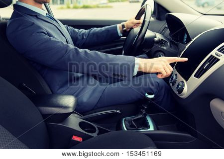 transport, business trip, technology and people concept - close up of young man in suit driving car and pointing finger to blank black computer screen on dashboard