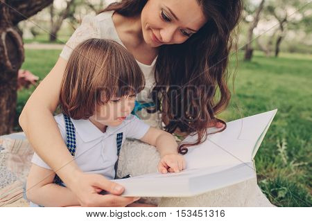 mother reading book to toddler son outdoor in spring garden. Family spending time together on picnic. Parent teaching kids on summer vacation.