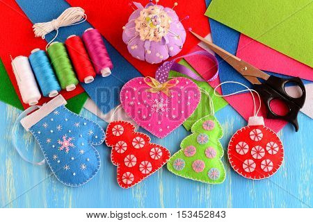 Christmas tree decorations crafts. Felt pink heart, red and green Christmas tree, blue mitten, red ball on wooden background. Sewing supplies, thread, scissors, needle, felt sheets, pincushion, pins