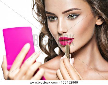 Woman applying lipstick looking at mirror. Beautiful girl makes makeup