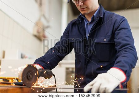 Portrait of a worker using a grinding machine to cut a metal plate