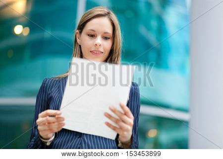 Businesswoman outdoor reading a document