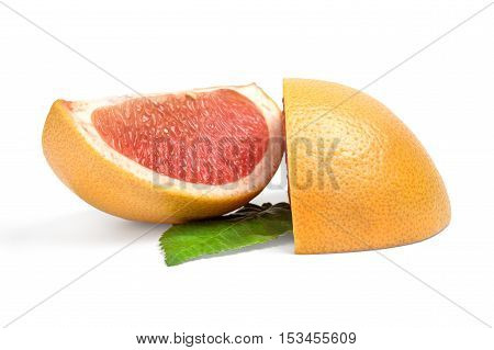 Two wedges of grapefruit on white background with green leaf.