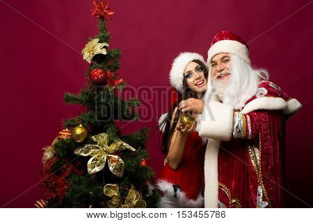 Happy santa claus man and pretty girl in new year red suit decorate Christmas tree with xmas ball