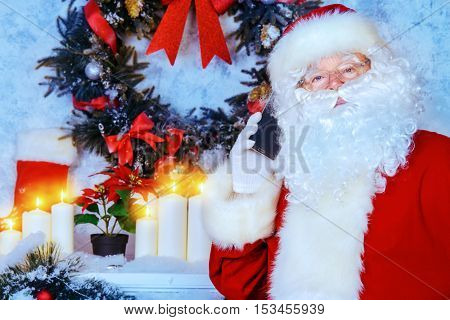 Jolly Santa Claus standing by the fireplace in a room, decorated for Christmas and talking on the phone.