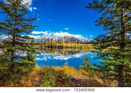 The coniferous forest at around lake. The concept of hiking. Mountains and scenic clouds are reflected in the water