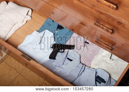 Gun Hidden In A Drawer Full Of Shirt At Home