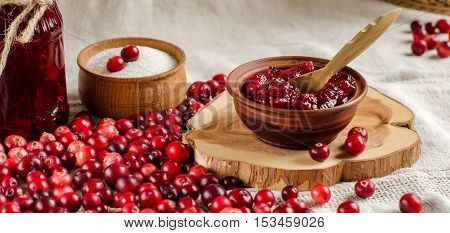 Fresh cranberries. The red berries. Jam from cranberries in a bowl with a spoon. Jar of jam glass. Light linen tablecloth.