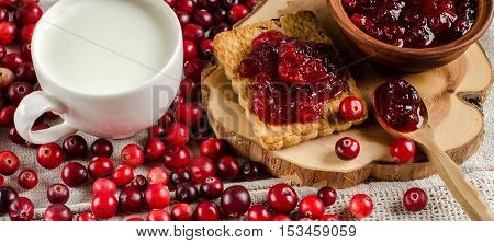 Red berries scattered on the table. Cranberry. Biscuits and jam from cranberries on the Board. White Cup of milk. A bright background.