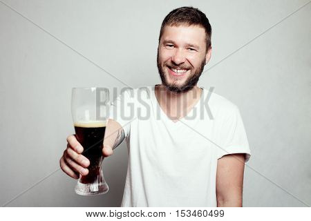 Drunk tattooed bearded man in a white T-shirt isolated on a grey background. A guy with a glass. smiling man happy