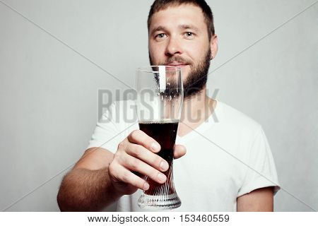 Drunk tattooed bearded man in a white T-shirt isolated on a grey background. A guy with a glass
