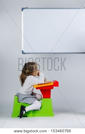 photo of little girl looking at marker board