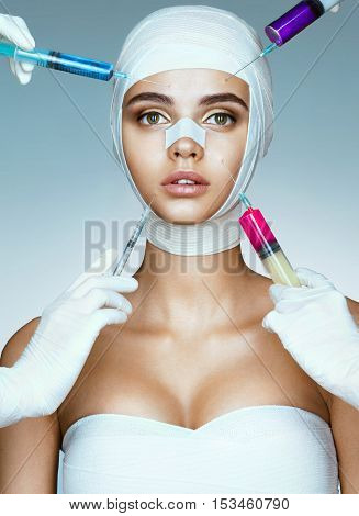 Pretty woman in medical bandages and beauticians hands with syringes making botox injection in her face. Rejuvenation therapy concept.