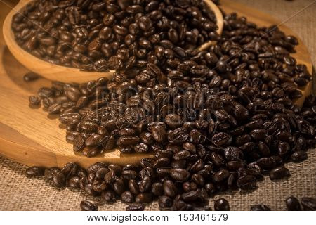 Coffee beans in wood plate place on hemp sack