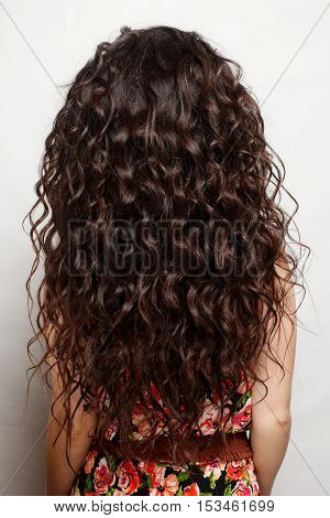 back of the woman with long brown curly hair with healthy shine wearing a leather dress over a studio background.
