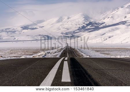 Scenic winter view with the winding asphalt road in the steppe on a background of mountains covered with snow
