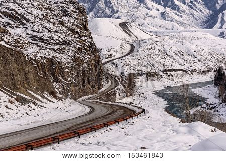 Scenic winter view with the winding asphalt road river and trees on a background of mountains covered with snow