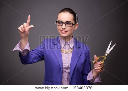 Young woman with scissors against gray background