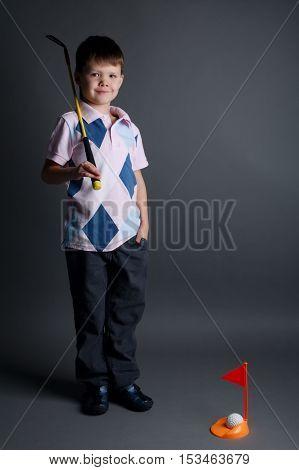 photo of little boy playing mini golf