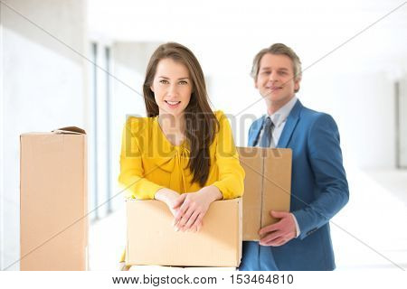 Portrait of confident businesswoman and male colleague with cardboard boxes in new office